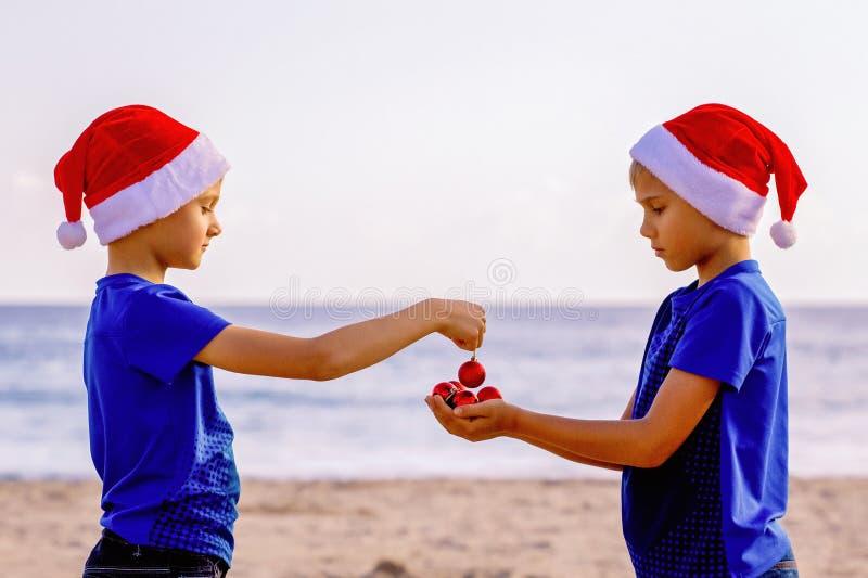 Festa di Natale Bambini in cappelli rossi di Santa alla spiaggia soleggiata fotografie stock