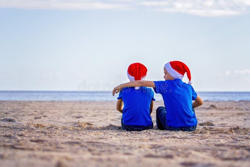 Festa di Natale I bambini in cappelli rossi di Santa si siedono abbracciare alla spiaggia soleggiata immagine stock libera da diritti
