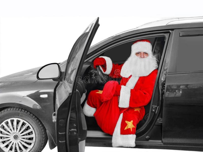 Festa di nuovo anno Santa Claus - l'autista si siede dietro la ruota dell'automobile con una borsa dei regali fotografia stock libera da diritti