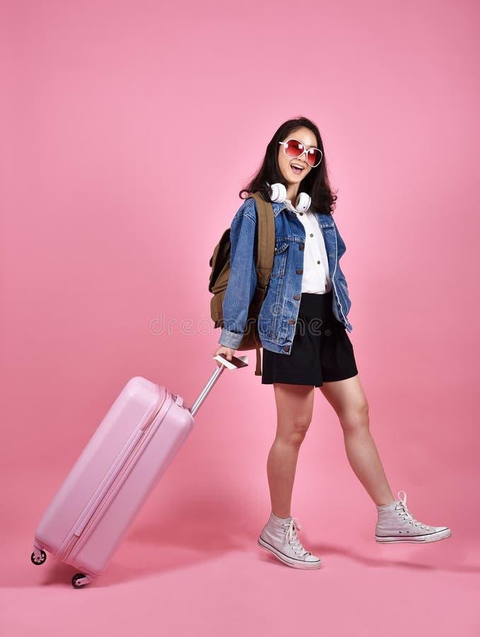 Festa e concetto di viaggio, viaggiatore sorridente della donna che tiene valigia ed il documento rosa del passaporto immagini stock libere da diritti