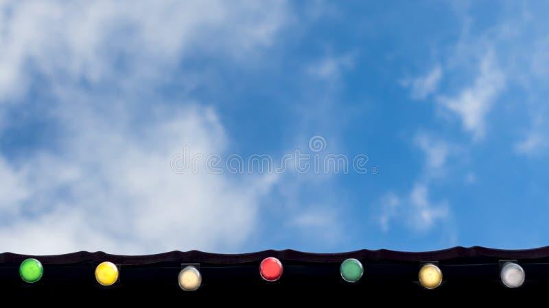 Festa felice, concetto del fondo di celebrazione di evento: linea di lampadine variopinte cercare, sul cielo blu e sul bianco del fotografie stock