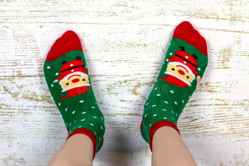 Festa felice Nuovo anno e Buon Natale Gambe del bambino in calzini rossi e verdi con Santa Claus fotografie stock