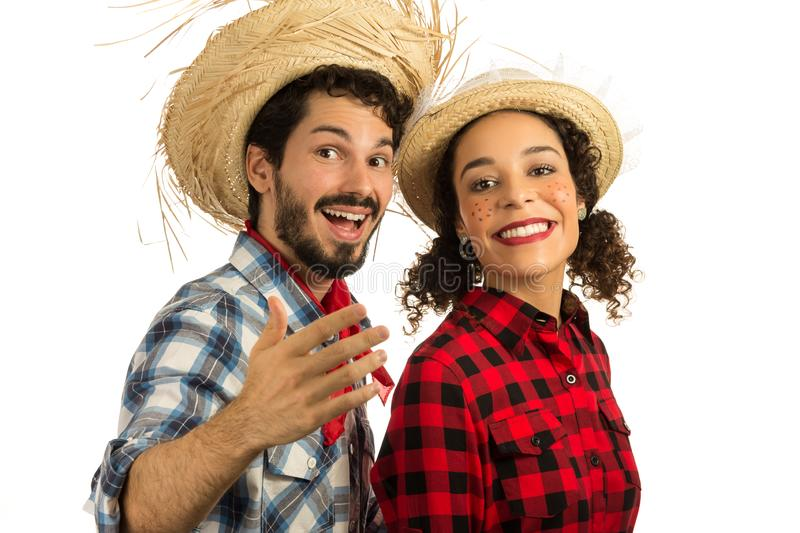 Festa Junina is June party in Brazil.  Beautiful couple wearing plaid clothes, traditional of the celebration. Man is inviting you royalty free stock images