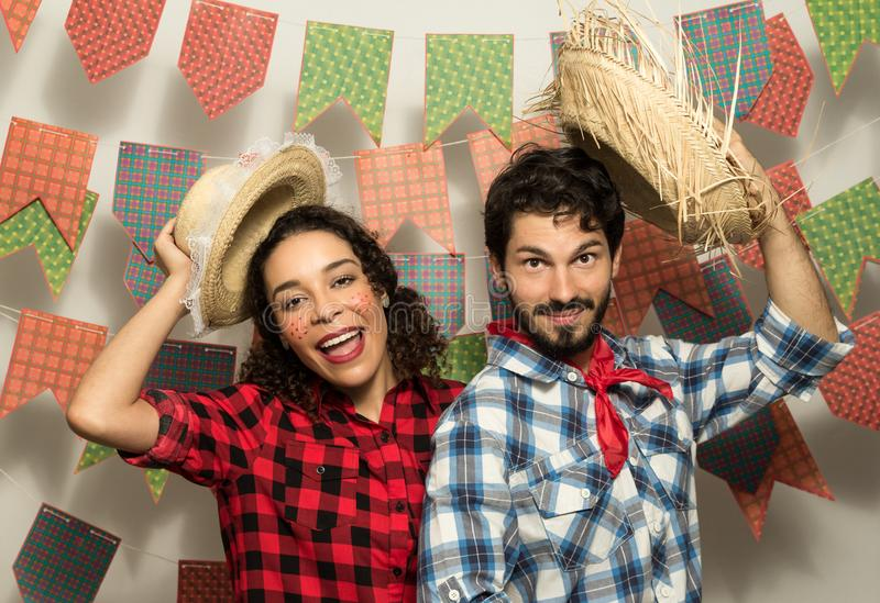 Festa Junina is June party in Brazil. Couple wearing typical clothes is waving with the straw hat. They are inviting to the party royalty free stock image