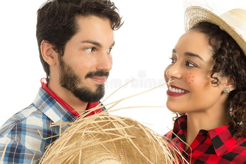 Festa Junina is June party in Brazil. In love couple is looking at each other intensely. Man with beard holding straw hat. Brazilian Festa Junina. June party in stock photography