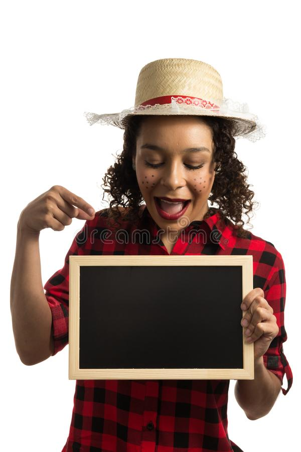 Festa Junina is June party in Brazil. .Pretty girl pointing at the blackboard. Expression of surprise stock image