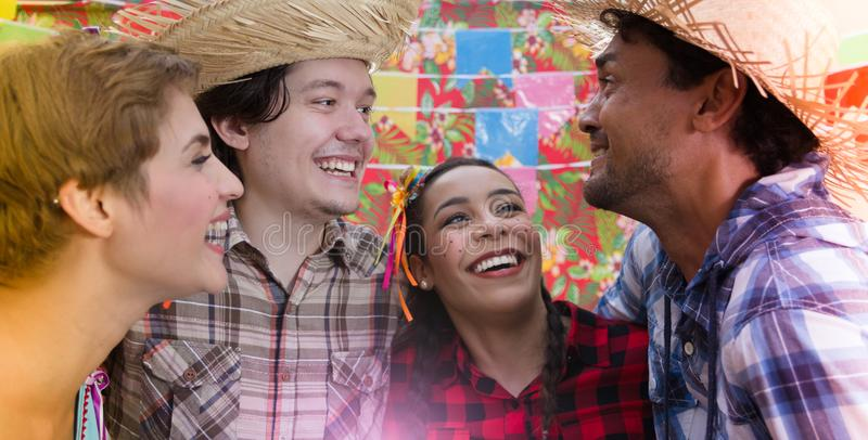 Festa Junina: June Party. People in plaid costume at traditional holiday. Flags and decor in background stock images