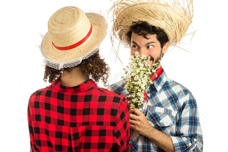 Festa Junina: party in Brazil. Brazilian couple wearing plaid shirts. Man is offering flowers to girl dressing checked pattern stock photos