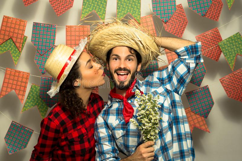 Festa Junina: party in Brazil. Man and woman dressing checked pattern clothes. Happy man gets a kiss from pretty woman stock images