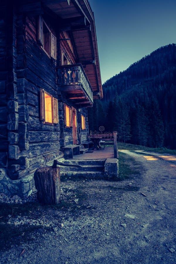 Festa nelle alpi: Capanna di legno rustica dell'azienda agricola nella notte fotografie stock