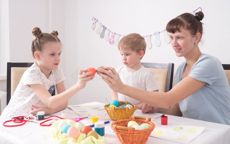 Festa Pasqua della famiglia: La mamma e la figlia stanno battendo le uova di Pasqua immagini stock libere da diritti