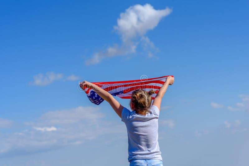 Festa patriottica Bambino felice, ragazza sveglia del piccolo bambino con la bandiera americana U.S.A. celebra il quarto luglio immagine stock