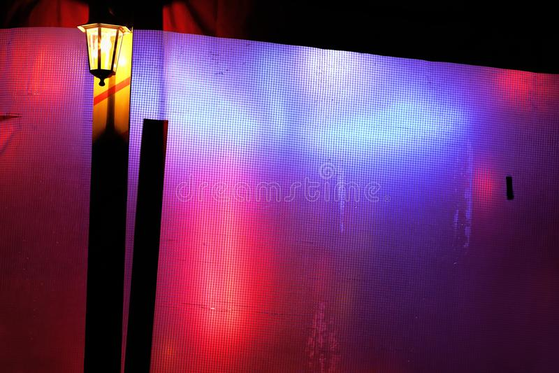 Festa staketet med reflexioner av mångfärgad bakgrund för neonljus royaltyfria bilder