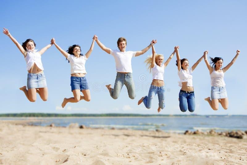 Festar unga vänner för gruppen som tycker om en strand, på semester FolkH royaltyfria foton