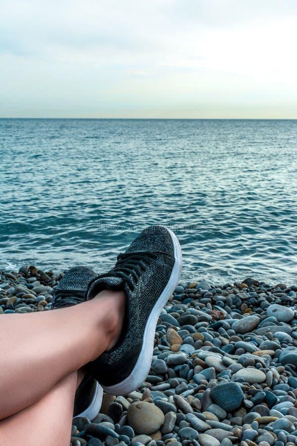 Feste alla menzogne di riposo sul mare, gambe della concetto-giovane ragazza del mare, di vacanza e di viaggio in scarpe da tenni fotografie stock