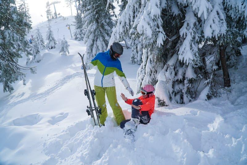 Feste di corsa con gli sci della famiglia nell'inverno festa della figlia e della madre nelle montagne immagini stock