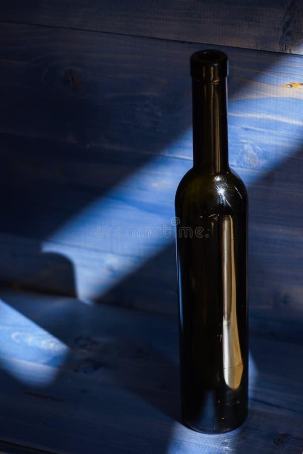 Feste e concetto di celebrazione Il vino imbottiglia l'ombra su fondo di legno blu scuro Bevanda alcolica in vetro scuro fotografia stock