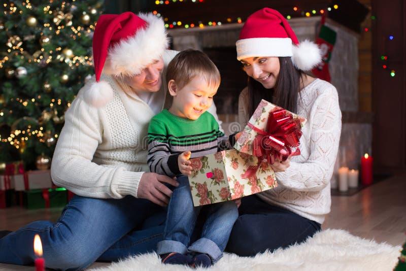 Feste, presente, concetto di natale - contenitore di regalo felice di apertura del ragazzo della madre, del padre e del bambino immagine stock libera da diritti