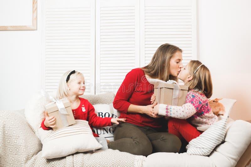Feste, presente, natale, natale, concetto di compleanno - madre felice e ragazza del bambino con il contenitore di regalo immagine stock