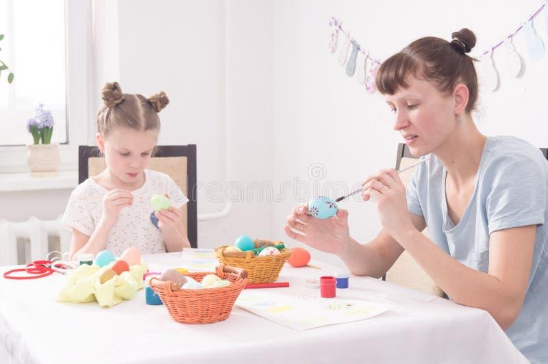 Feste religiose: Uova di Pasqua della pittura della figlia e della mamma fotografie stock