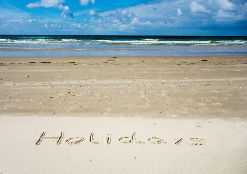 Feste scritte in sabbia con il mare nei precedenti e nel cielo blu fotografia stock libera da diritti