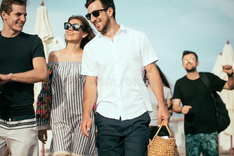 feste, vacanza gruppo di amici divertendosi sulla spiaggia, sulla camminata, sulla birra della bevanda, sul sorridere e sull'abbr fotografia stock