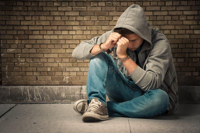 Festgehaltener Jugendlicher mit Handschellen lizenzfreie stockfotografie