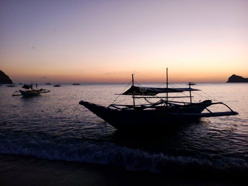 Festgemachte Ausleger nahe Pundaquit setzen in den Dämmerungen nach Sonnenuntergang nahe San Antonio, Philippinen auf den Strand stockfotografie