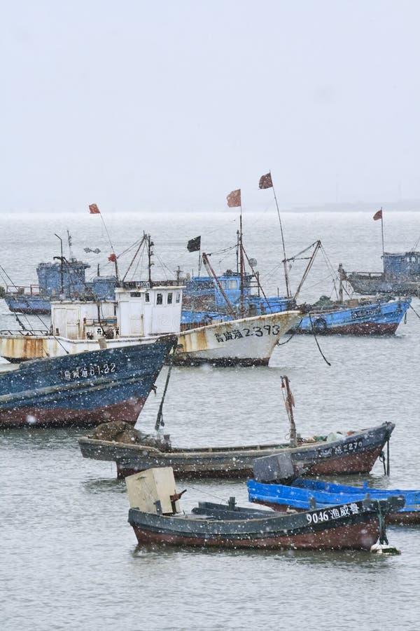 Festgemachte Schiffe in einem Schneeschauer, Weihai, China lizenzfreies stockbild