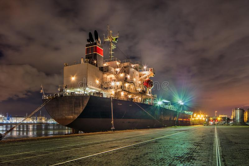 Festgemachter Öltanker nachts mit einem drastischen bewölkten Himmel, Hafen von Antwerpen, Belgien stockbild