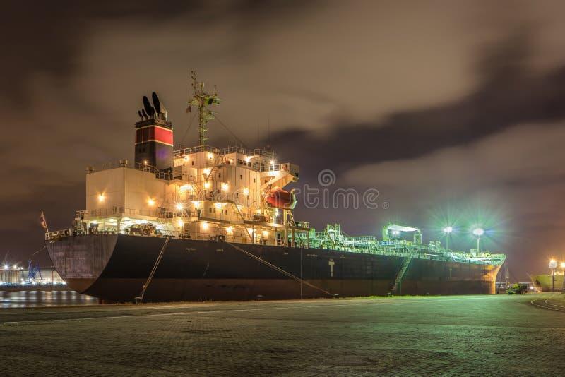 Festgemachter Öltanker nachts mit einem drastischen bewölkten Himmel, Hafen von Antwerpen, Belgien lizenzfreie stockfotografie