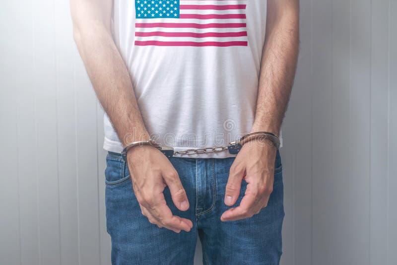 Festgenommener Mann mit den geohrfeigten Händen, die Hemd mit USA-Flagge tragen stockfotos