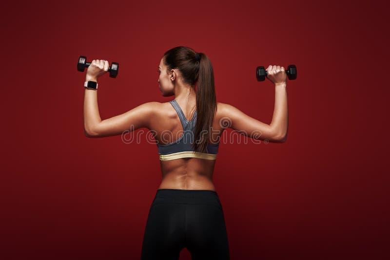 Festgestellt zu gewinnen Sportlerin hält die Dummköpfe, die über rotem Hintergrund stehen stockfoto