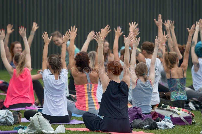 Festival da ioga no gramado no parque no centro da metrópole foto de stock