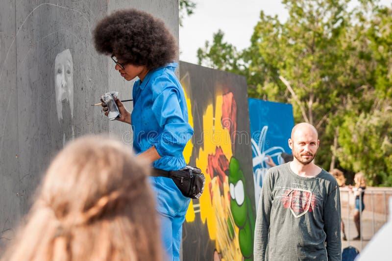 Festival de la pintada El cuadrado central de la ciudad La muchacha afroamericana hermosa joven Sandra Sambo dibuja la pintada fotos de archivo