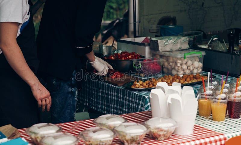 Festival de nourriture de rue équipez couper en tranches la tomate, faisant cuire les aliments de préparation rapide tak photos stock
