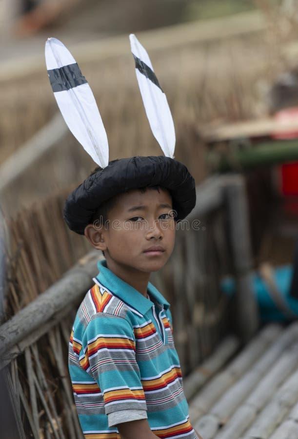 Festival del Hornbill Nagaland, la India: 1 de diciembre de 2013: Niño joven del Naga con un sombrero hermoso que presenta para l imagen de archivo