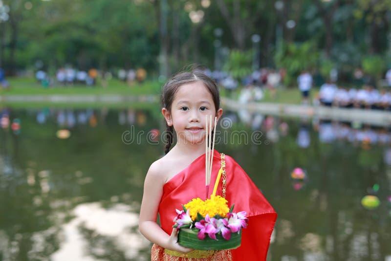 Festival di Loy Krathong, ragazza asiatica del bambino in vestito tradizionale tailandese con il krathong della tenuta per la dea fotografie stock