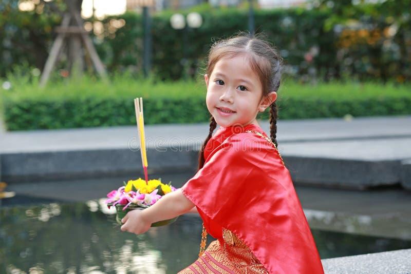 Festival di Loy Krathong, ragazza asiatica del bambino in vestito tradizionale tailandese con il krathong della tenuta per la dea immagine stock