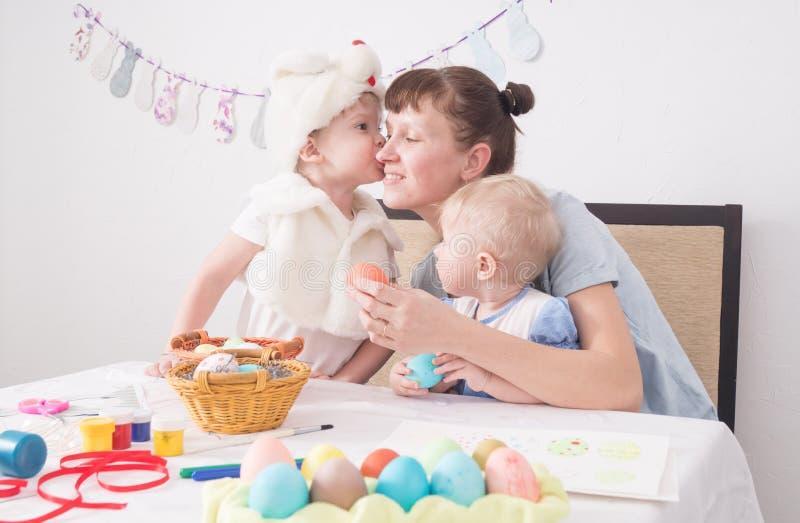 Festival di Pasqua: La famiglia alla tavola dipinge le uova di Pasqua Il figlio nel costume del coniglio di Pasqua bacia il suo fotografie stock