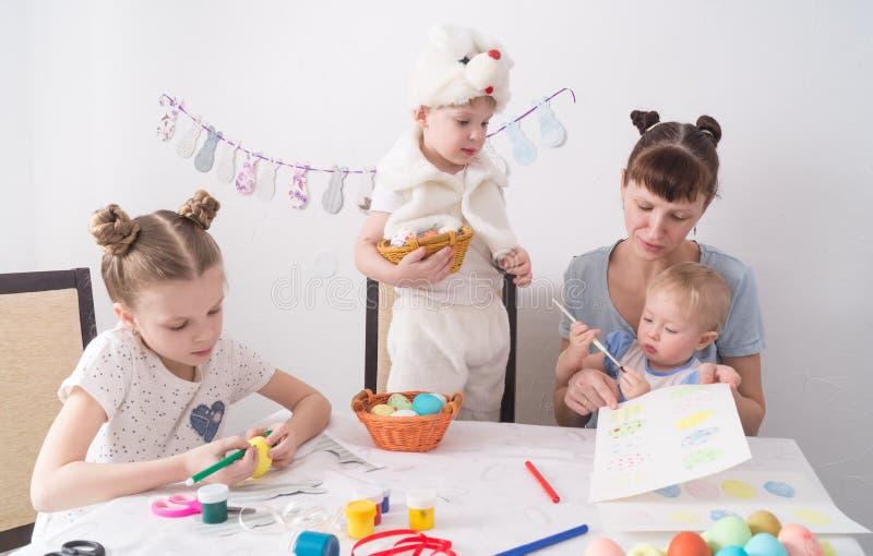 Festival di Pasqua: La famiglia alla tavola La mamma mostra ai bambini come dipingere le uova di Pasqua immagine stock