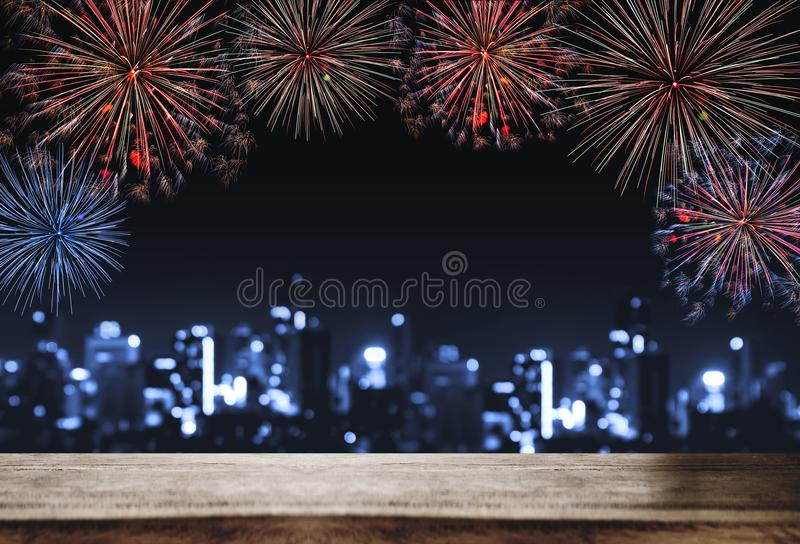 Festival fireworks at night in the city, wooden desk with Bokeh lights of building at night. For Holiday festival, New years. And celebration backgrounds royalty free stock photography