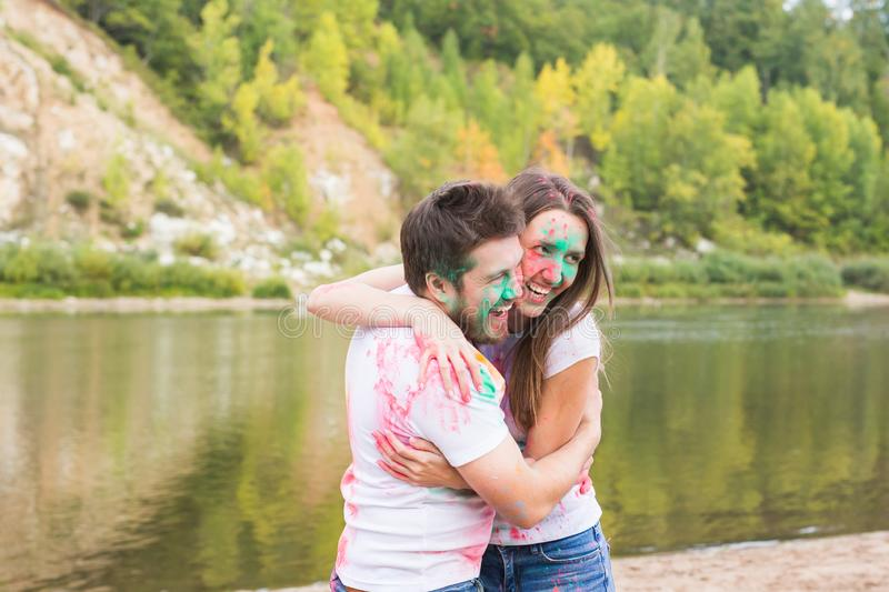 Festival holi, holidays, tourism and nature concept - Portrait of woman and man covered multi-colored dust royalty free stock photo