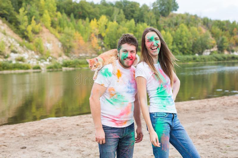 Festival holi, holidays, tourism, pet and nature concept - Portrait of woman and man with cat covered multi-colored dust royalty free stock photo