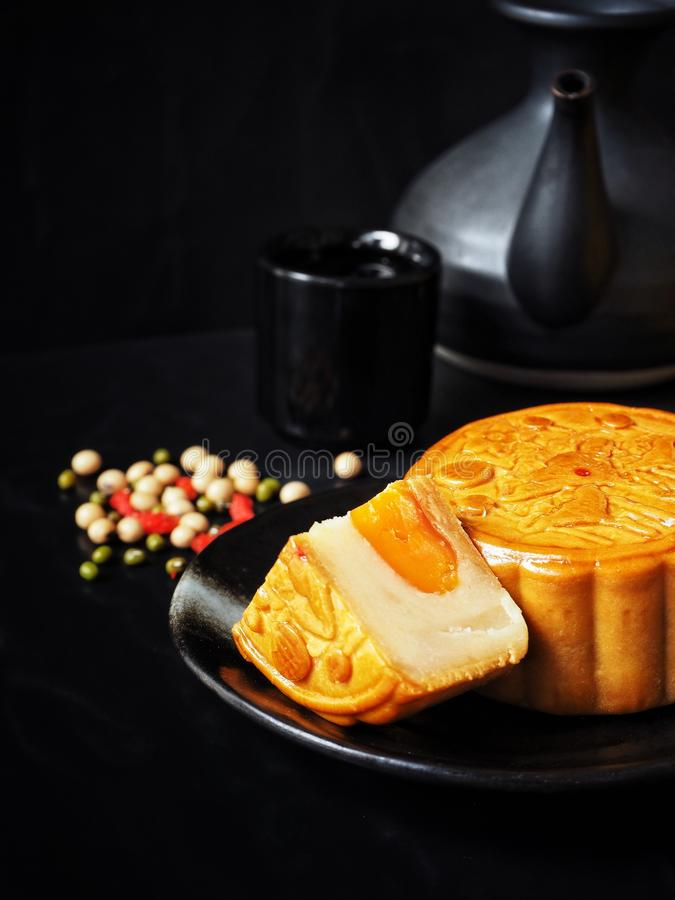 Festival moon cake with hot tea on black background royalty free stock photography