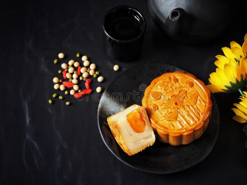Festival moon cake with hot tea on black background stock images