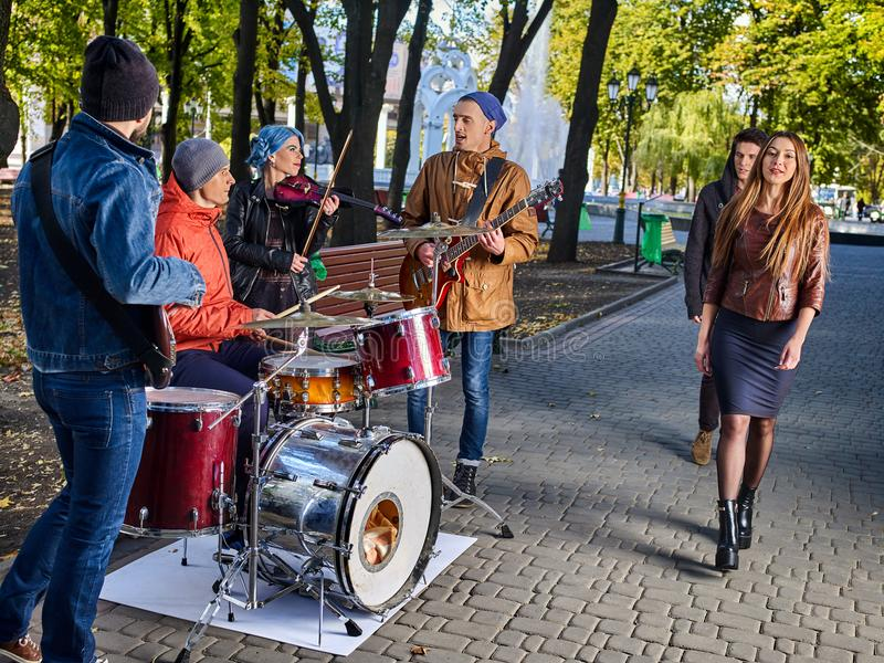 Festival music band. Friends playing on instruments city autumn park. stock image