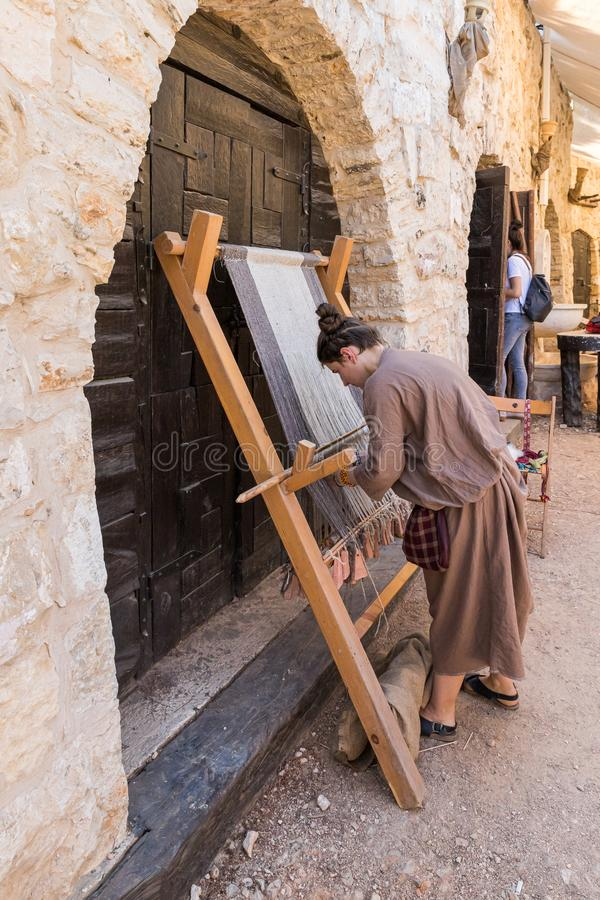 Festival participant demonstrates work on a medieval loom at the annual festival Jerusalem Knights. Jerusalem, Israel, September 30, 2019 : Festival participant royalty free stock photography