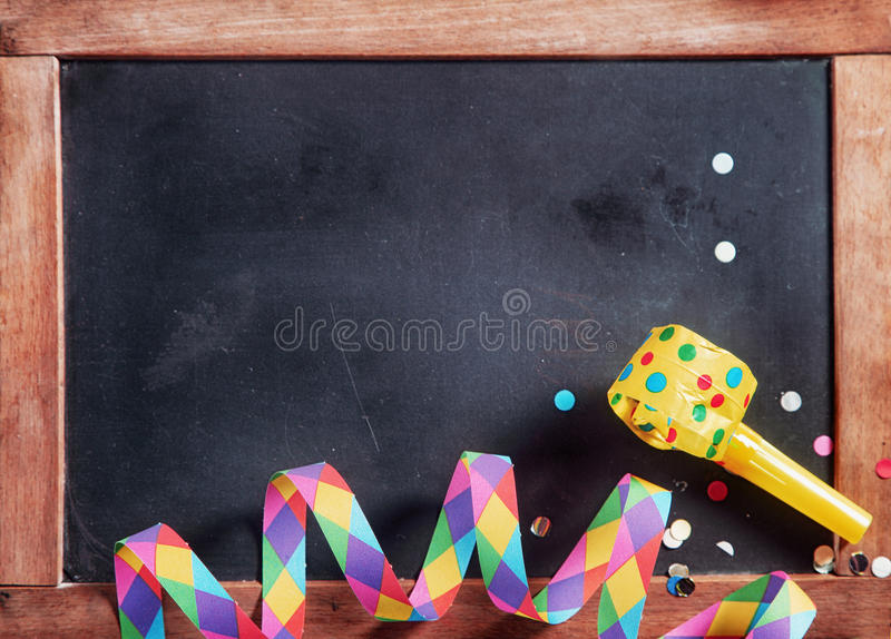 Festival Streamer, Confetti and Whistle on Board. Close up Colored Festival Paper Streamer, Confetti and Whistle on Black Board. Emphasizing Copy Space stock photo