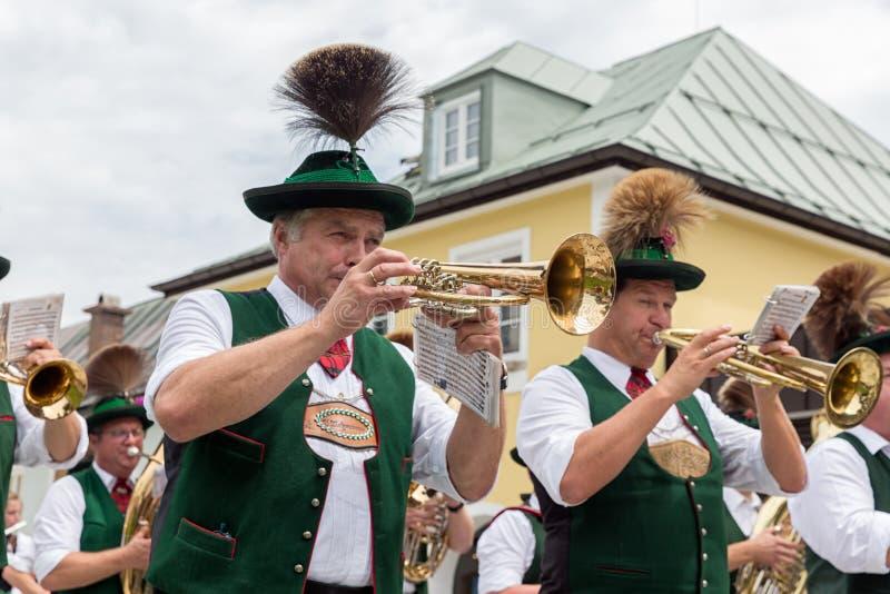 Festivalen med ståtar av fanfar och folk i traditonaldräkter arkivfoto